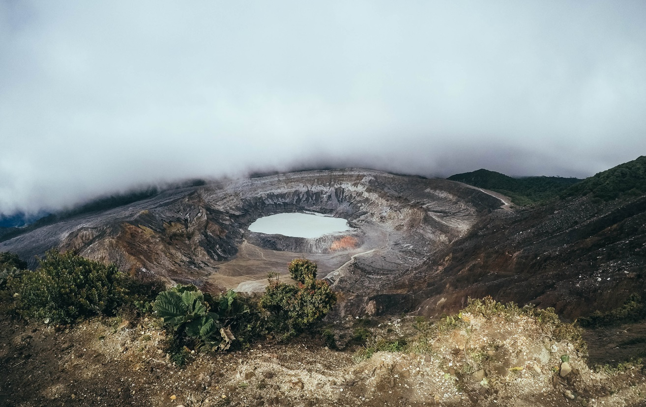 Crater surrounded by fog and black sand
