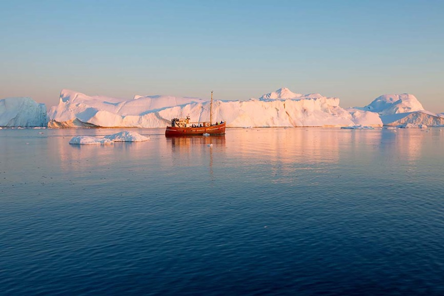 Research vessel in front of iceberg in Greenland
