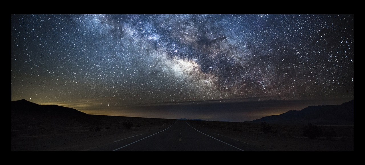 Night sky with the milky way and stars over an empty road, USA.