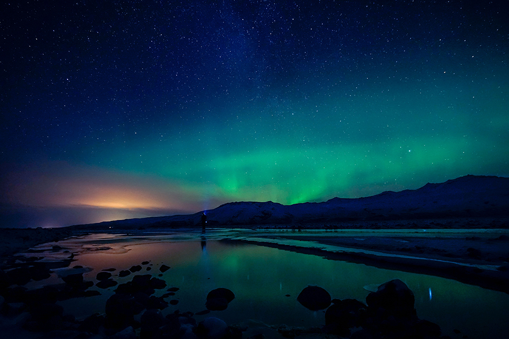 Northern lights over coast with hills
