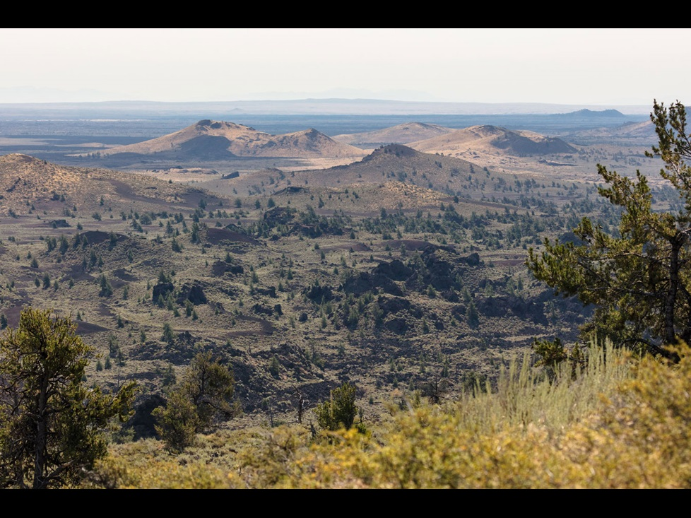 Landscape photo showing the volcanoes of Craters of the Moon National Monument in the distance
