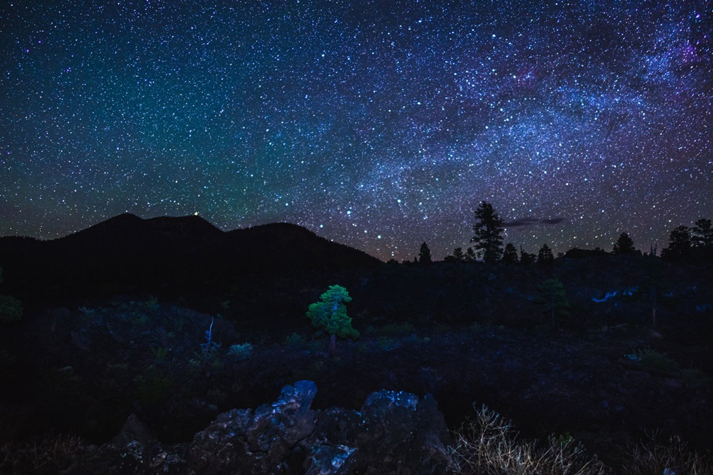 The night sky full of stars with the dark outline of O'Leary Peak at Sunset Crater National Monument