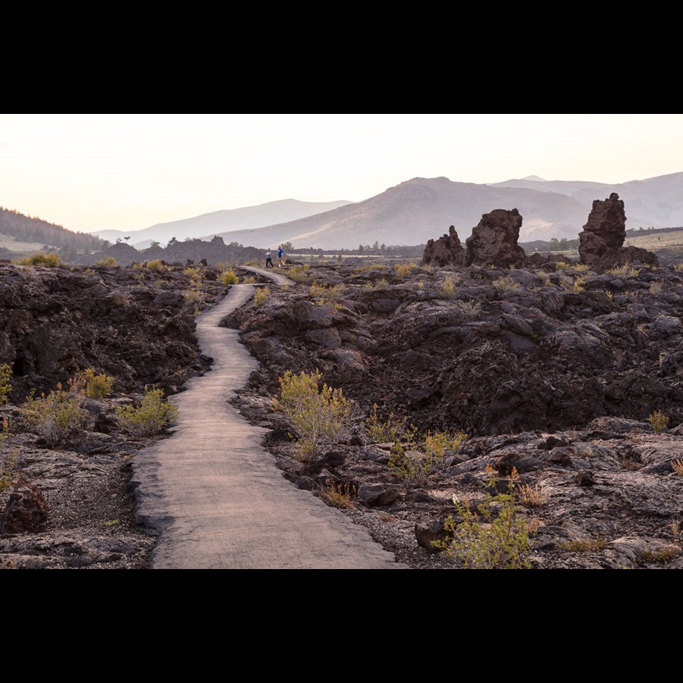 A hiking trail with two hikers in the distance at Craters of the Moon National Monument