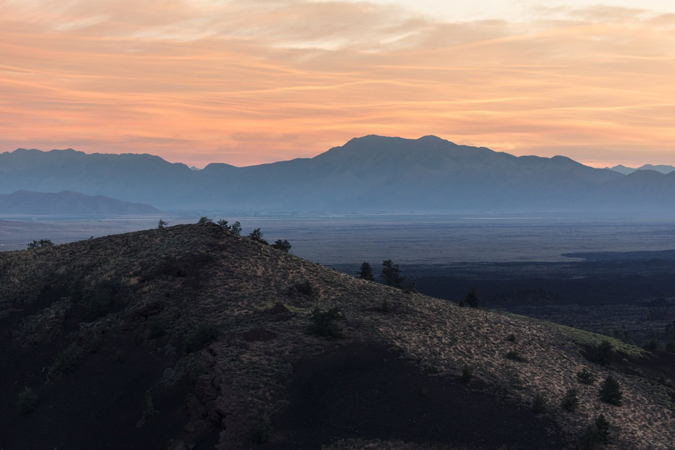 A sunrise behind a volcanic cone in Craters of the Moon National Monument