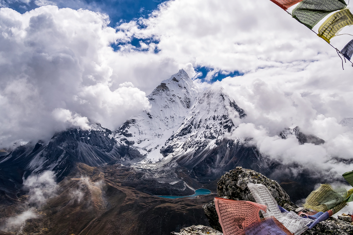A snow-covered mountain surrounded by clouds with colorful fabric in the foreground