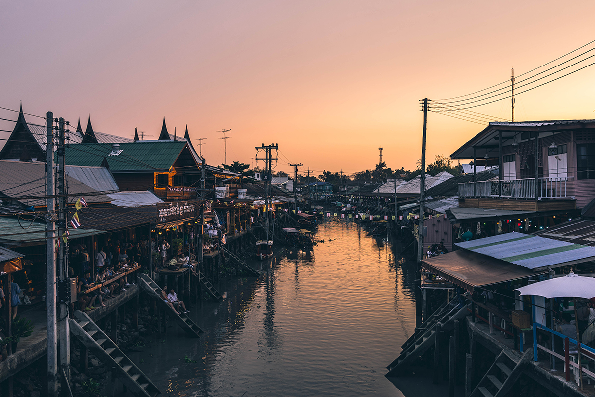 A Thai floating marketing over calm water at sunset