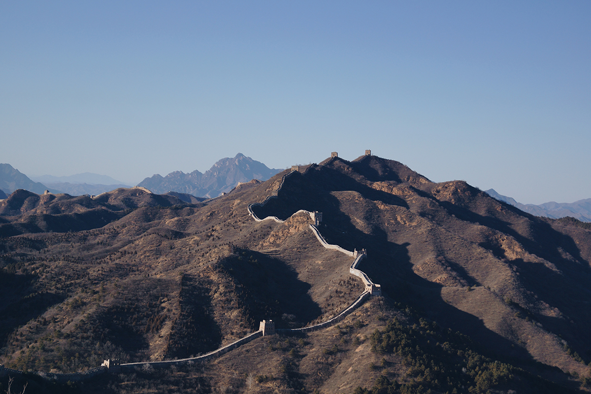 Brown mountains under a blue sky with the Great Wall of China