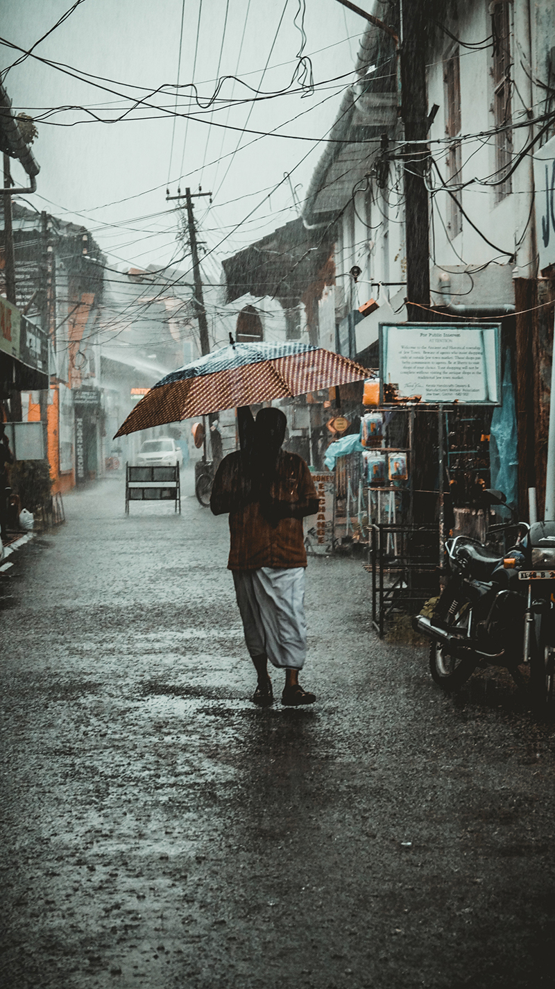 Man standing in a street under an umbrella in a rain storm