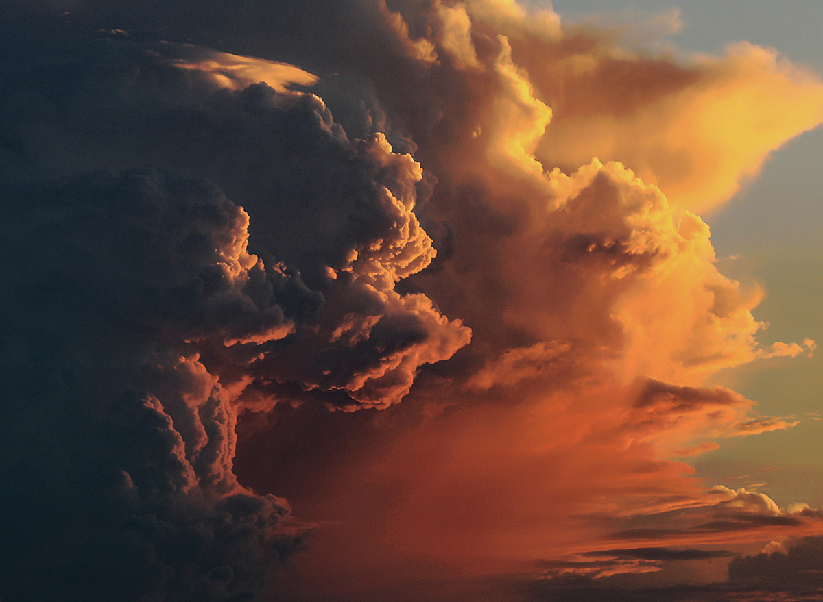 large storm clouds with light cast by setting sun