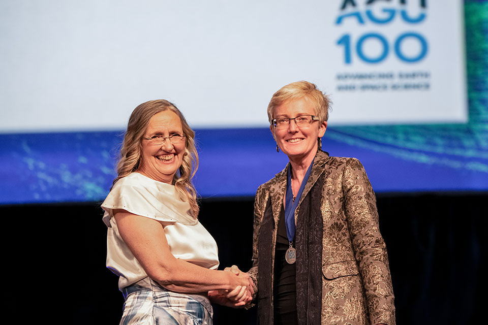 Woman fellow shakes hands with AGU president Robin Bell