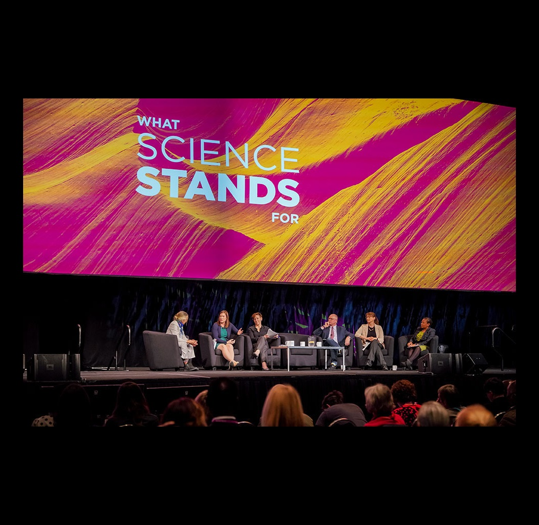 "Panel session sits on stage in front of a screen that says ""What Science Stands For"""