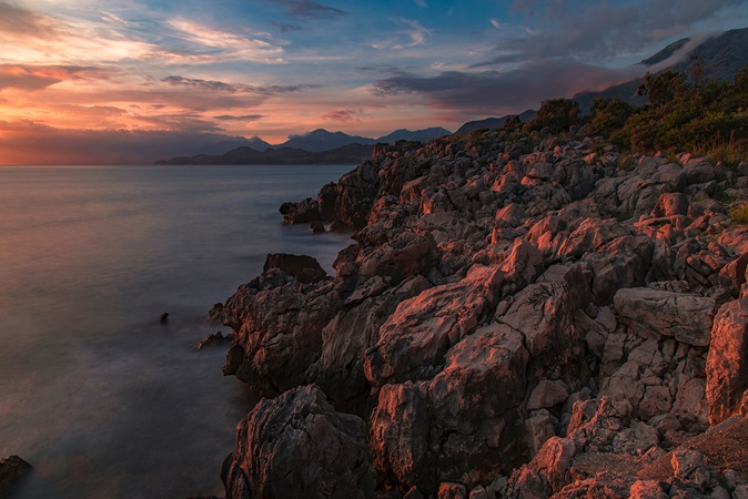 Rocky coastline with clouds and a pink lighting