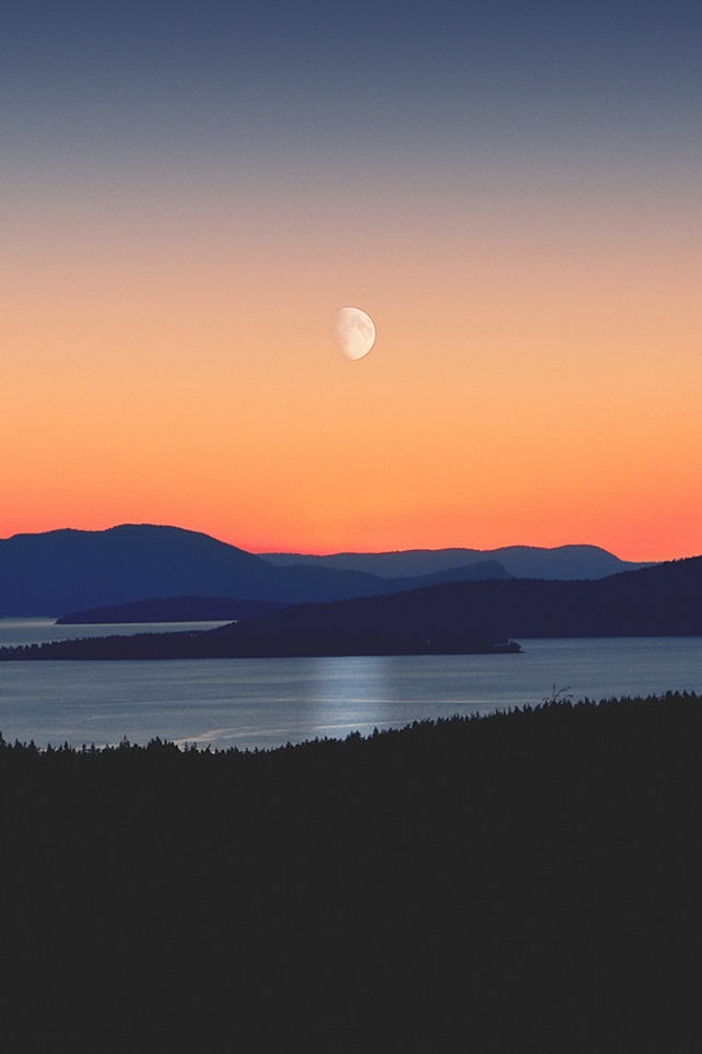 Water with hills underneath a gradient sky and moon