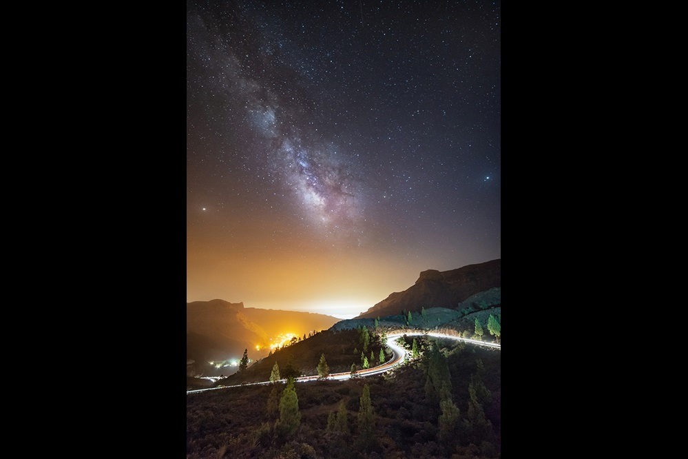 Cars driving up a curvy mountain road under a starry sky