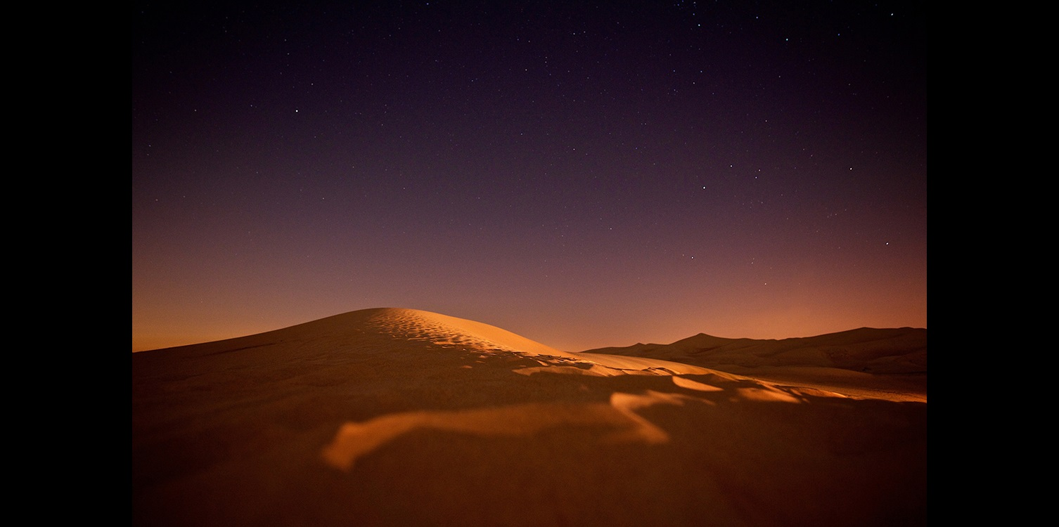 Desert dunes under a starry night scare