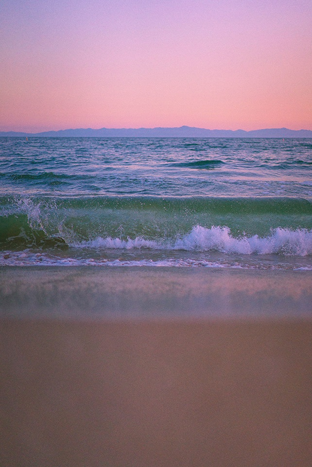 Waves crashing on shore under a pink sky at sunset