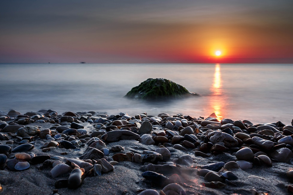 Rocks on shore line with sun reflecting on water