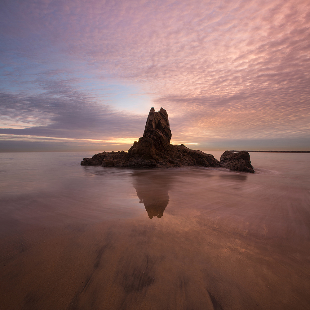Rocky island in water under pink clouds
