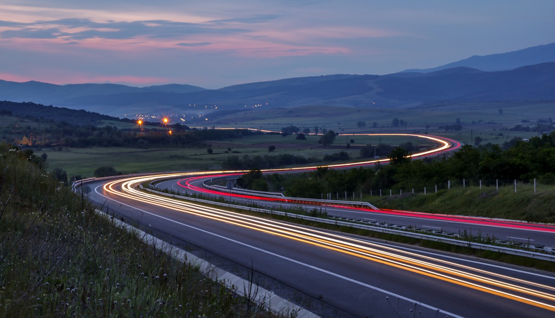 Cars driving through valley at dusk with light beams