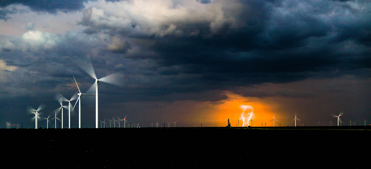 Wind turbines with lightning storm in background