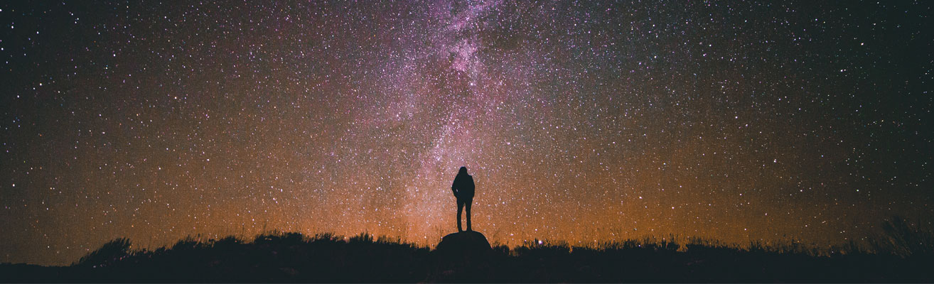silhouette of a person gazing up at stars and milky way
