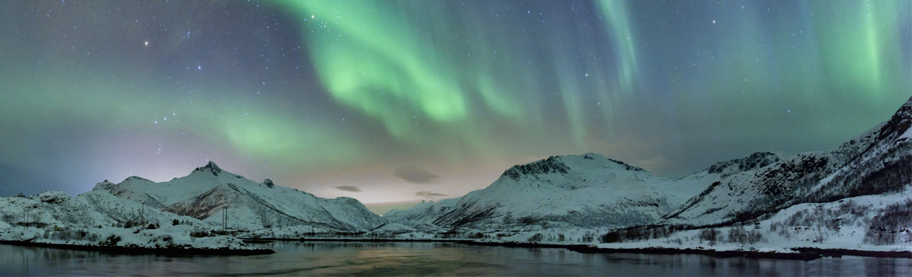 Northern Lights with snow covered mountains and a lake in the foreground