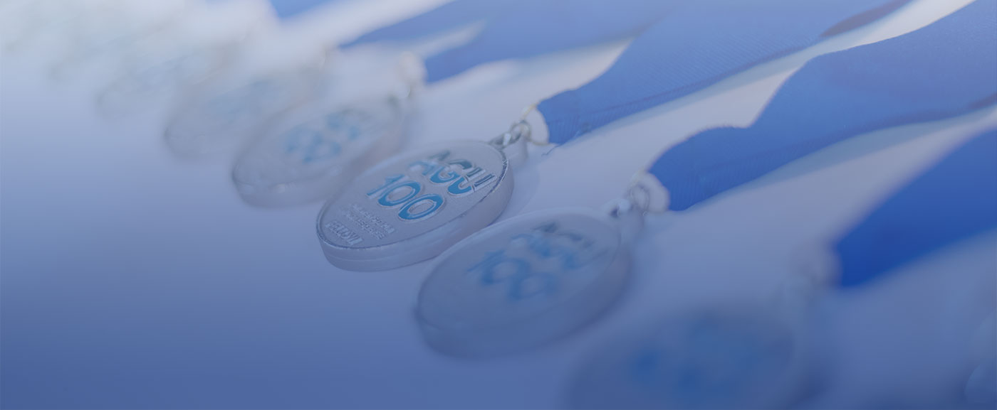 A photography of AGU Fellows medals with the AGU100 logo and blue ribbons laying across a white table.