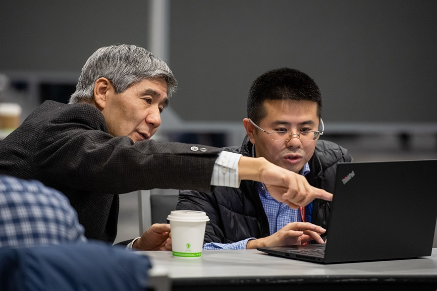 Male attendees in a discussion looking at computer