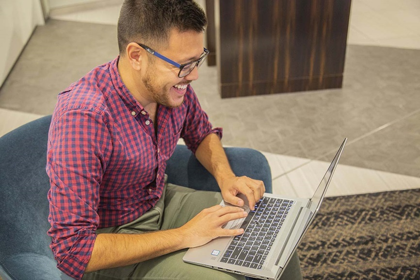 man smiling and typing on computer