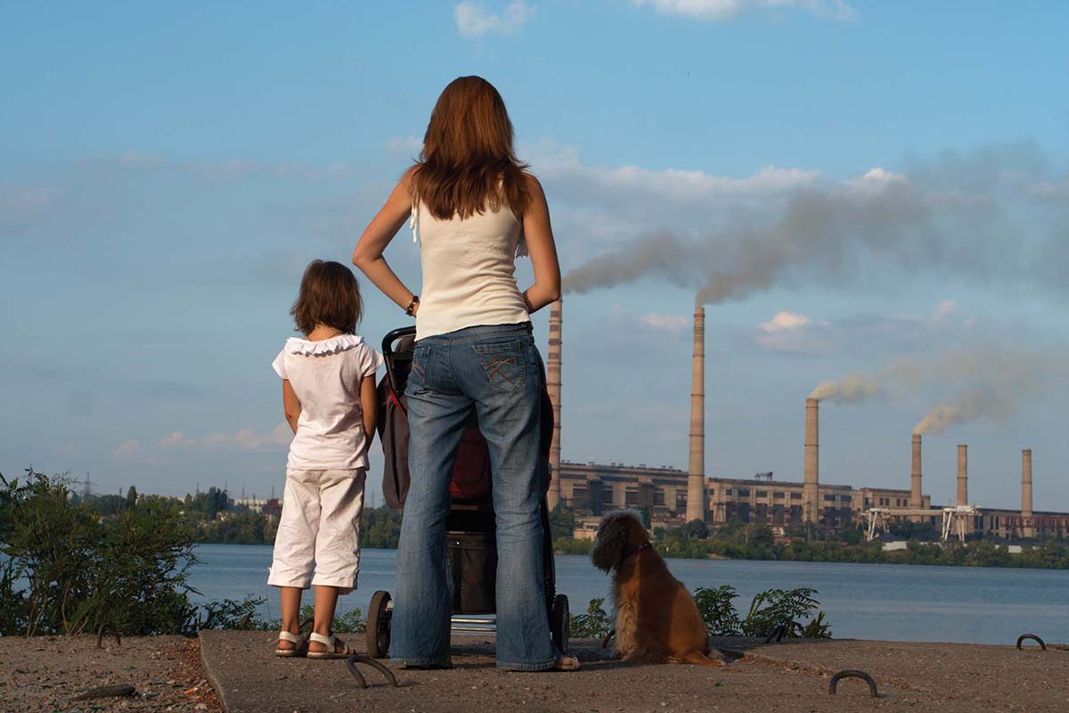 Mother with her kids and dog are looking over river and chimney-stalks polluting an air.
