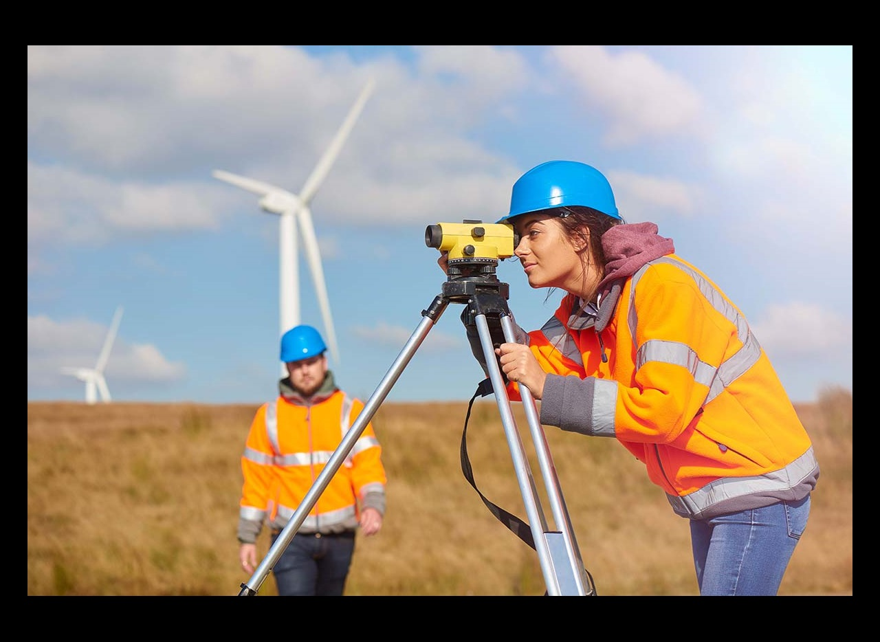 Female engineers looking through the level with wind turbines in background