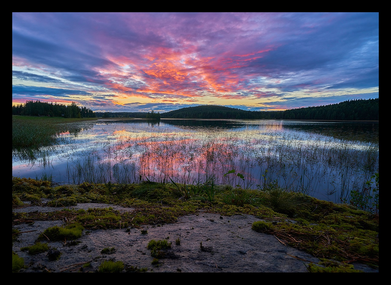 Lake with sunset and hills in background, Finland