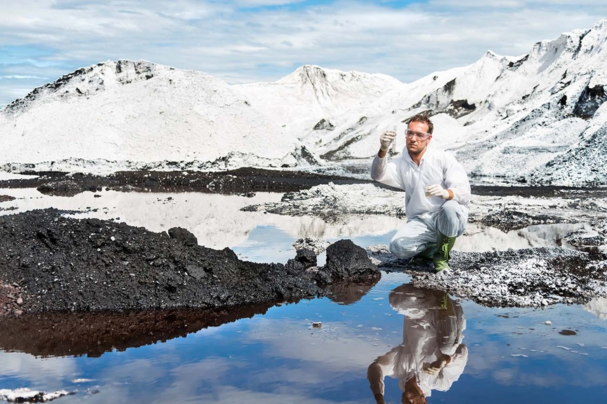 Man taking water sample with snow covered mountains in background