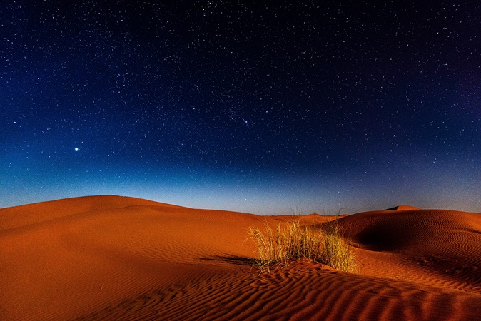 Nighttime stars over sandy desert dunes