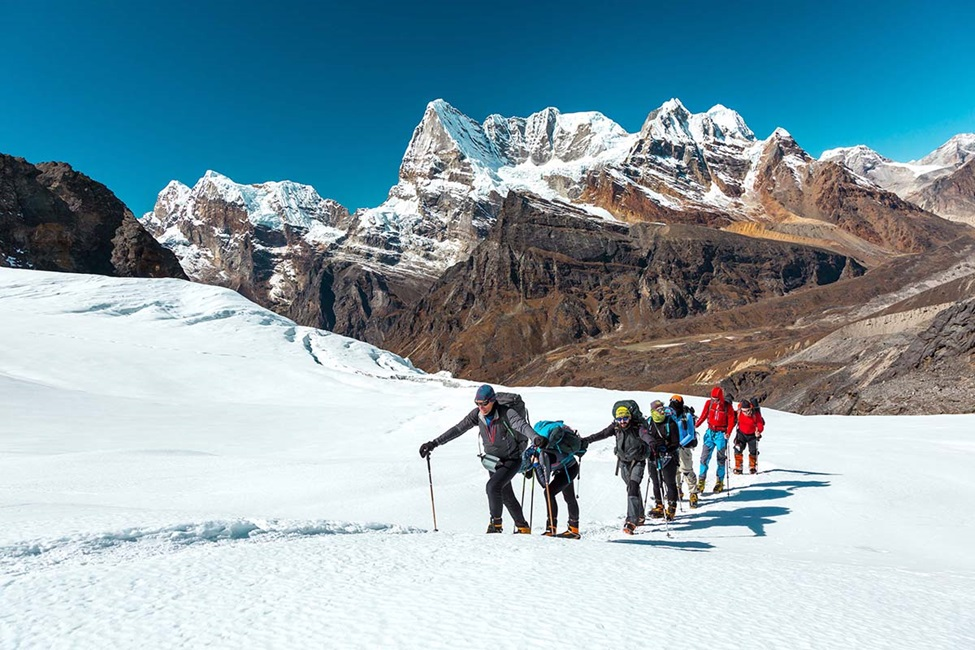 Group of People hiking up a snow covered mountain