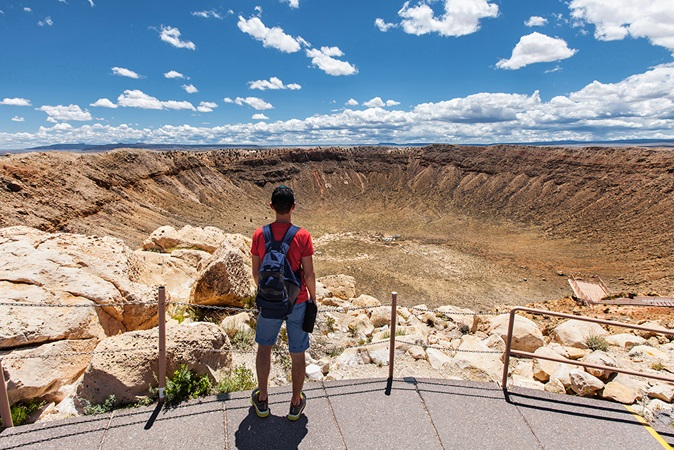 Man hiking in front of a crater