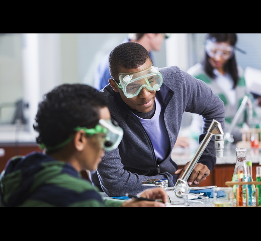 Teenage students in chemistry lab with safety goggles