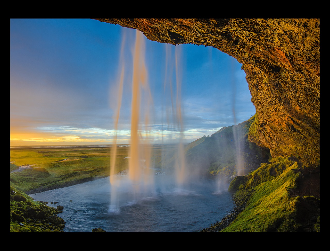 View of waterfall from inside a cave with sunlight