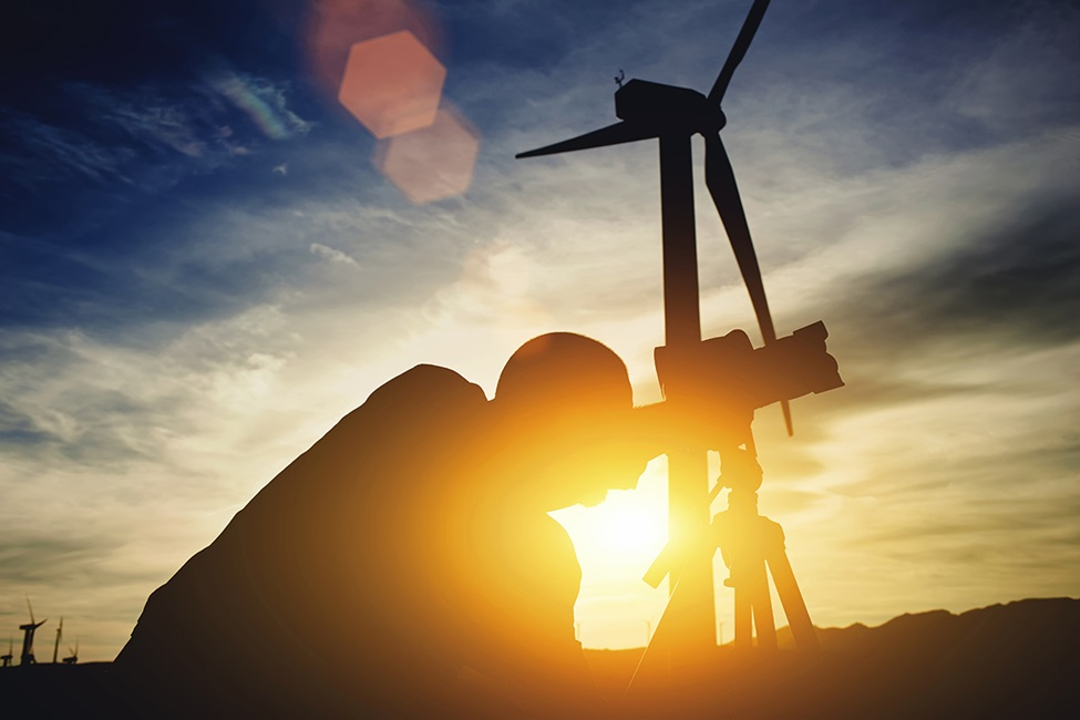 Geodesist using theodolitewhile standing against wind turbine and sunset