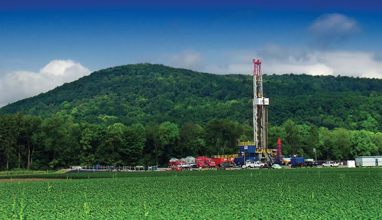 Shale drilling in front of green hill