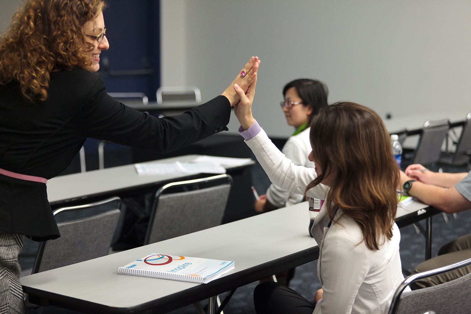 Teacher giving a student a high five in the classroom