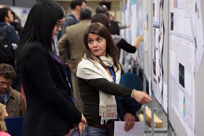 woman explaining poster to woman in poster hall