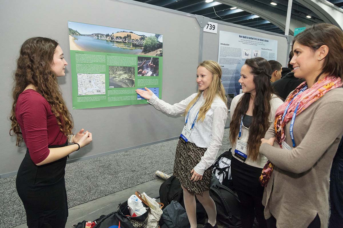 Female students discussing a poster