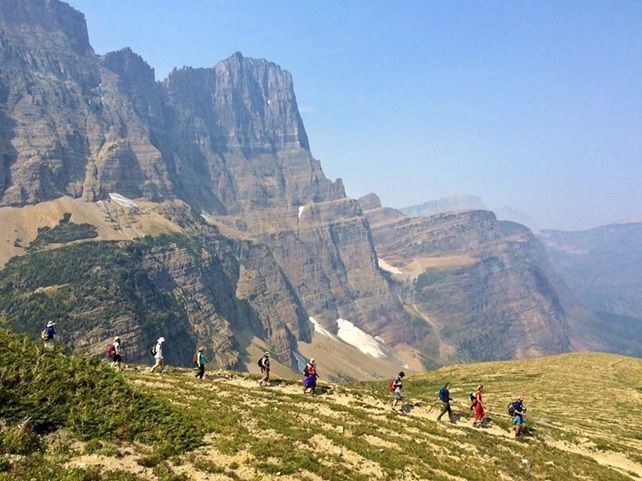 People hiking on trail along mountains and cliffs