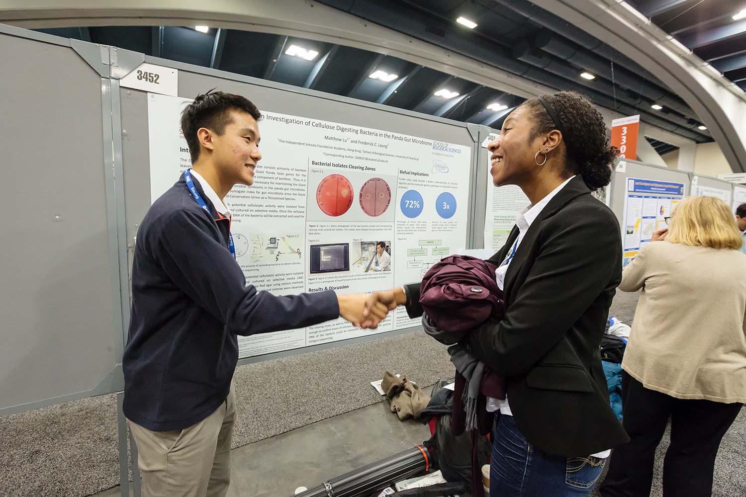 Two students shaking hands in poster hall