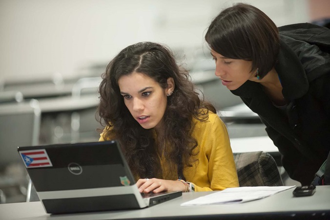 Teacher helping student on computer