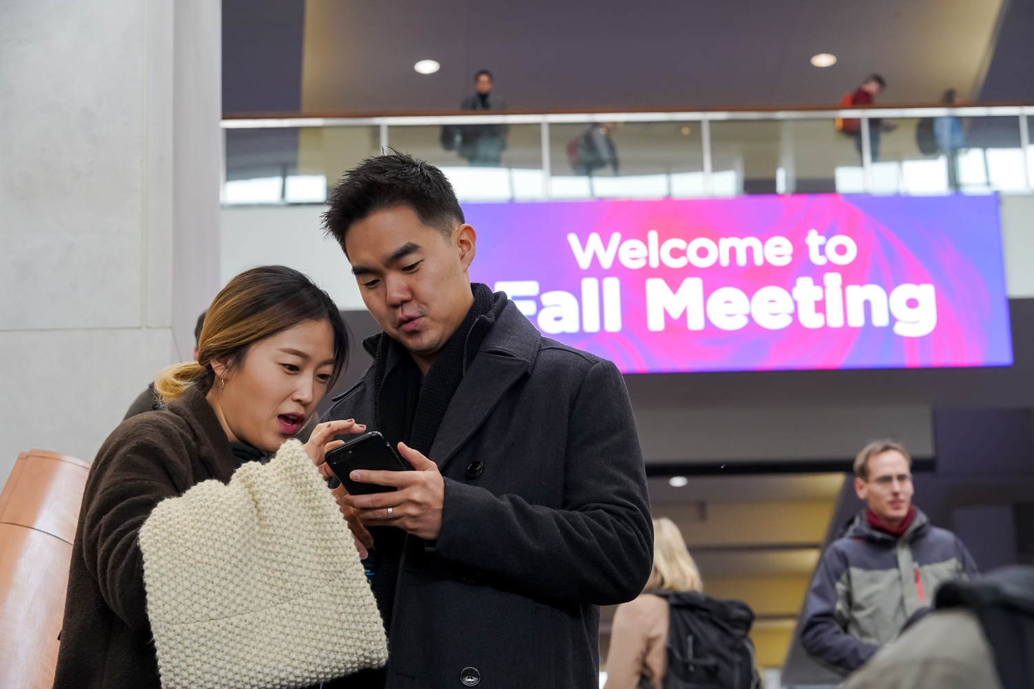 A man and a woman look at a phone with a Welcome to Fall Meeting banner behind them