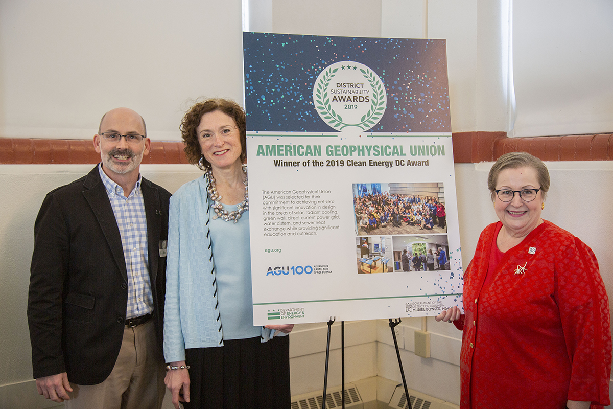 AGU leaders stand by a sign for the DC Sustainability awards
