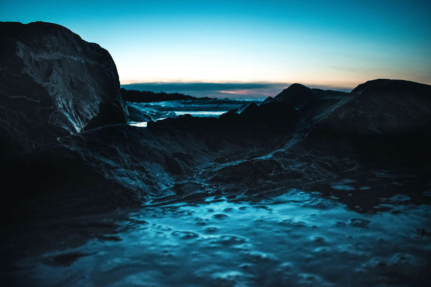 Rocky ocean with foam at sunset