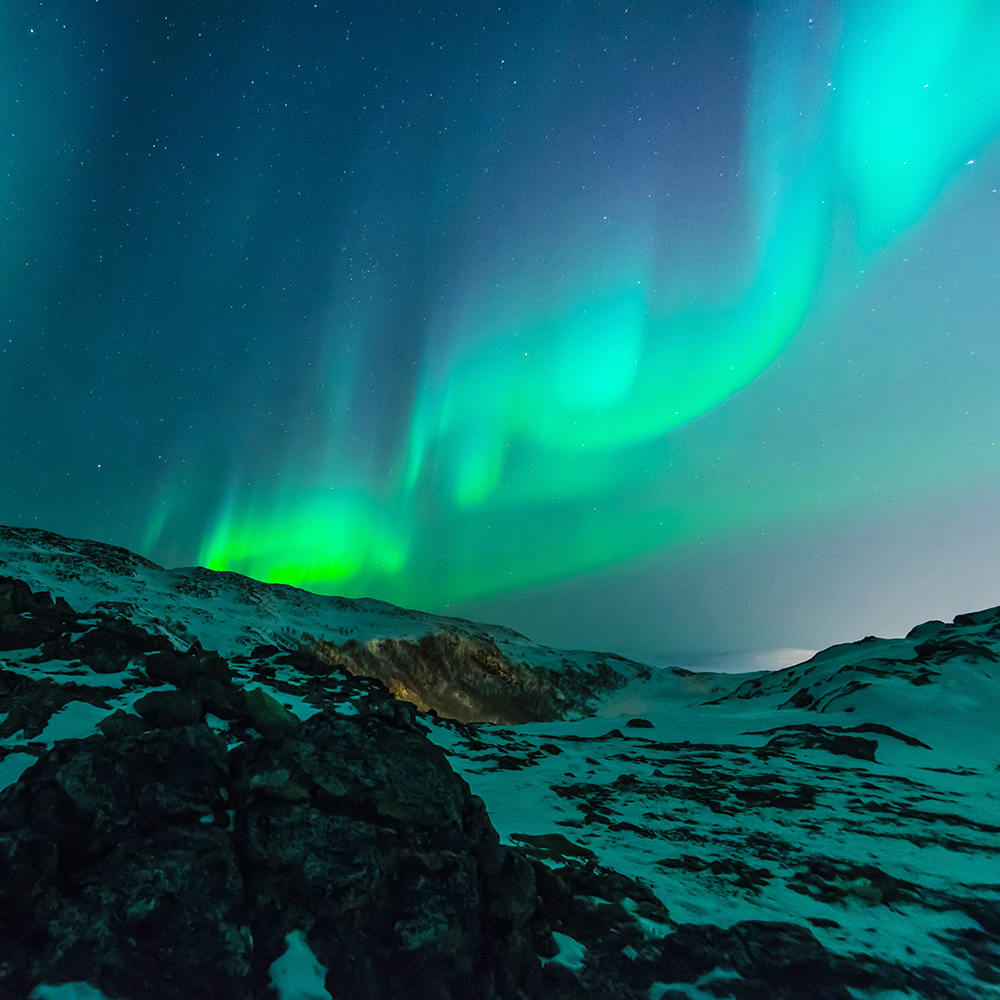 Aurora borealis with snow covered ground